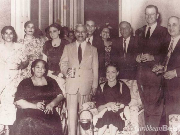 John Wayne (second from right) and his wife (seated, right) at a reception in 1951 at Roodal's Palace with Timothy Roodal (standing between chairs), Mrs Roodal (seated), family and friends. Photograph courtesy Adrian Camp-Campins