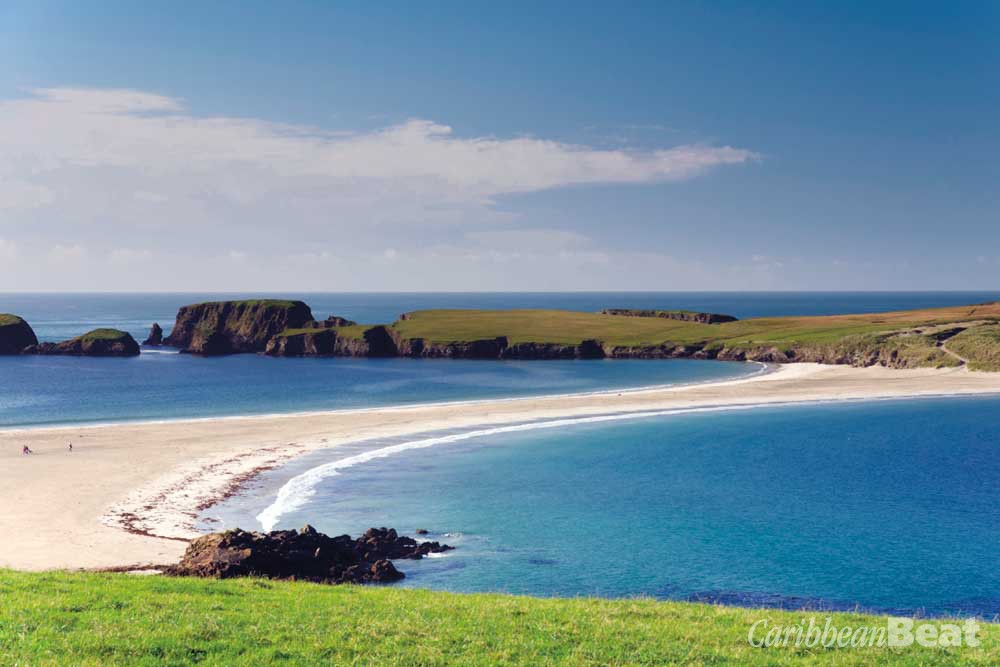 The white sand tombolo and brilliant blue water of St Ninian's Isle. Photograph © moorefam/istock.com