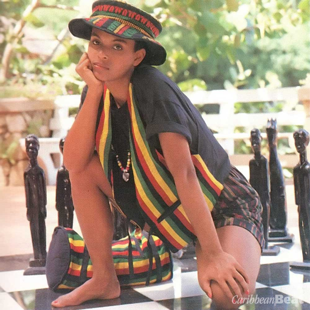 Janice's hand-woven vest ($36.00), shorts ($22.00), hat ($16.00) and back-pack in bold stripes and African prints are in the colours of the Rastafari. From Yard Gift Shop. Beads and crystals on a leather thong. Necklace by Collette Garrick for Wanders. Photograph by Steve Cohn