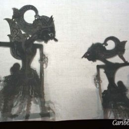In a wayang performance, the dalang sits behind a white screen, hidden from the audience, who see only the shadow silhouettes of the backlit puppets. Photography by Charles Chang