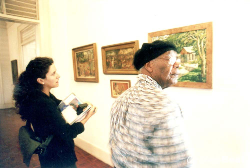 Huie reviews his exhibition with author Goodman. Photograph by Owen Minott