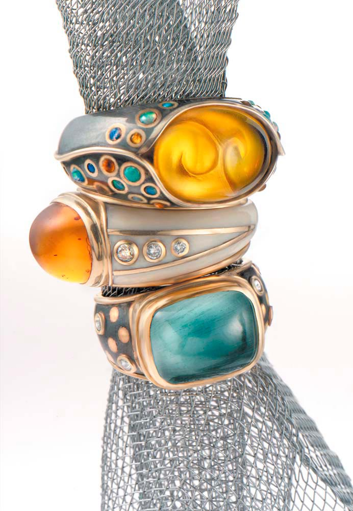 Rings (from the Alchemy collection): 18-carat gold, carved amber and silver inlaid with amber and opals;18-carat gold, amber and ivory inlaid with diamonds; aquamarine, 18-carat gold and oxidised silver inlaid with diamonds. Photograph by Woodbury & Associates