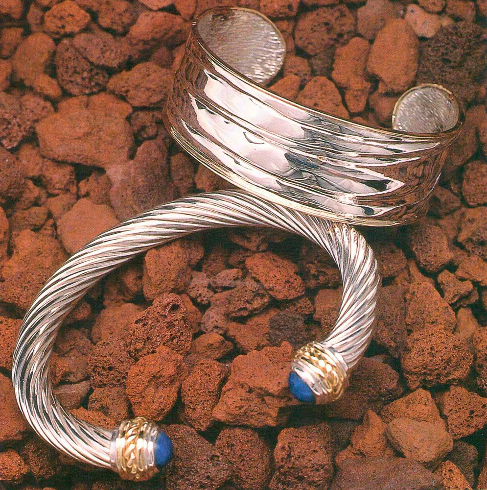 """Sterling silver slave band with 18-carat gold trim. Also sterling silver bracelet with 18-carat gold trim and lapis lazuli tips. Crafted by John """"Ding"""" King. Photograph by Eric Young"""