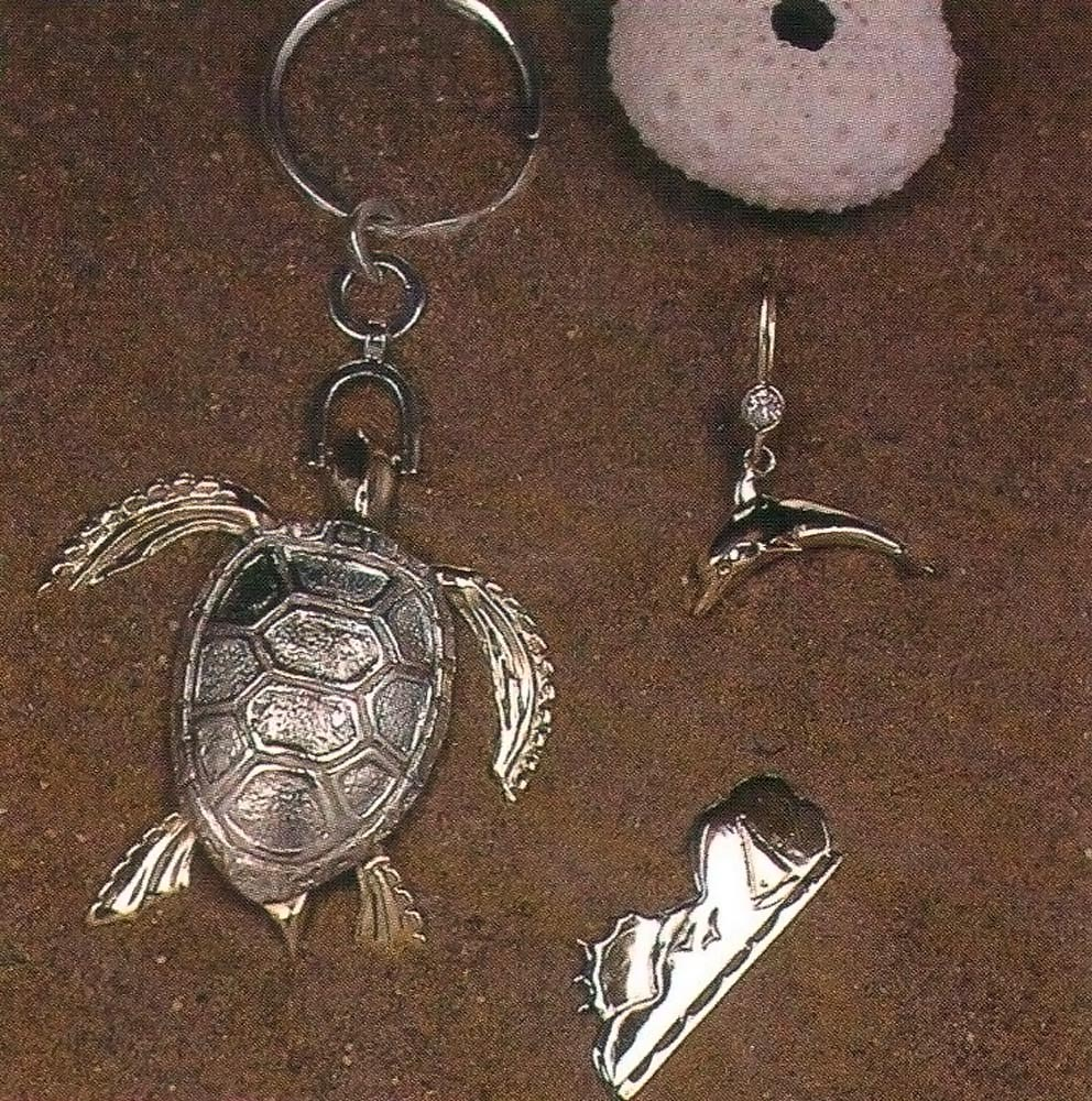 """18-ct gold dolphin earring with diamonds; sterling silver turtle key ring or pendant with moving 18-ct gold head and flippers; yellow and white gold pendant depicting """"fun in the sun"""".  Crafted by John """"Ding"""" King. Photograph by Eric Young"""