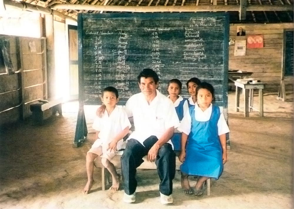 Dennis Paul poses with a few of his charges in the classroom. Photograph by Anna Nicholas