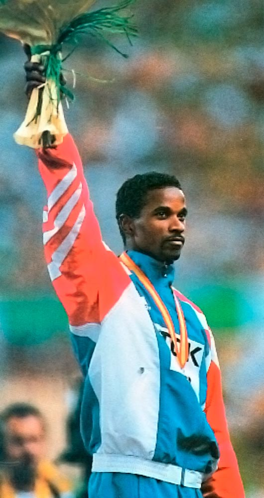 Ivan Pedroso, Cuba's long jump champion, receives gold in Seville, 1999. Photograph by Clive Mason/Allsport