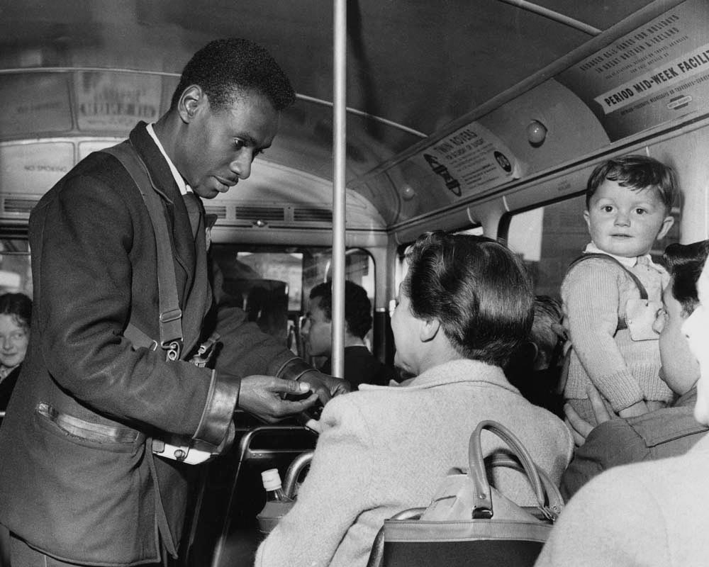A West Indian conductor on a London bus in the 1950s. Photo by Corbis Images