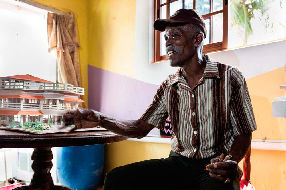 Curwin Callender holds a saffron root, grown in his own yard. He is sitting next to a model of the heritage centre that the Merikin Heritage Foundation hopes to raise the funds to build. Photo by Marlon Rouse