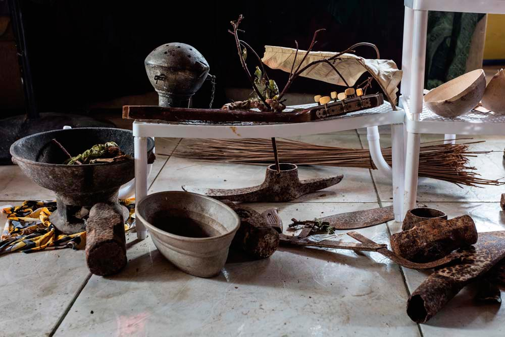 Curwin Callender's collection of Merikin artefacts, which includes a coalpot, axe heads, hoe blades, and other implements, some thought to be over a hundred years old. Photo by Marlon Rouse