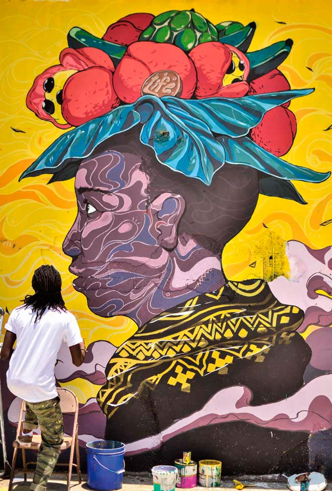 Artist Taj Francis works on a Paint Jamaica mural. Photo by Matthew Henry