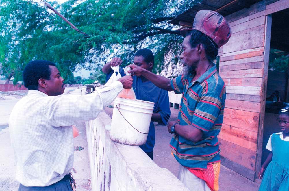 """Wilmott buys fresh juice at First Street, Trench Town, a place made famous by Bob Marley in Dread Natty Dread: """"Dally down to First Street . . ."""" Photograph by Wayne Tippetts"""