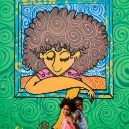 A girl from the neighbourhood, posing here with her friend, discovers an uncanny resemblance in artist Matthew Henry's mural. Photo by Matthew Henry