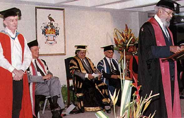 Peter Minshall (left) receives an honorary degree (1990). Left & right, seated: Sir Alister McIntyre & Sir Shridath Ramphal