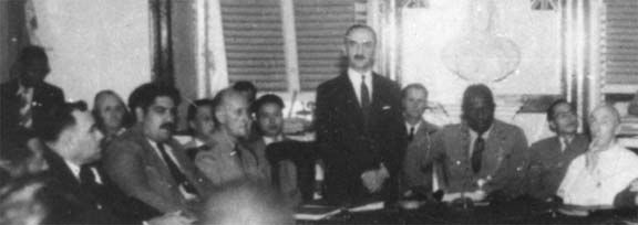 Acting Governor A.B. Wright speks on VE Day, 1945. Gomes is seated second from left. Photograph from the collection of Adrian Camps-Campins