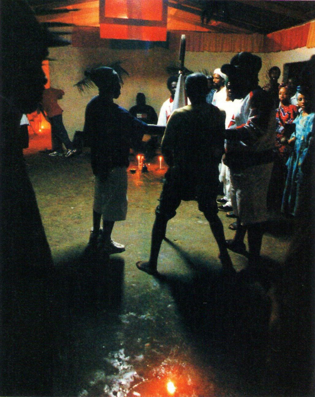 Shango makes his surprise appearance inside the shrine, having taken spirit possession outside in the storm. One of the chant leaders, left, and a master drummer help prepare him for the rest of his spiritual manifestion as Shango. Photograph by Horace Ové