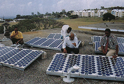 Oliver Headly (centre) and staff inspect solar collectors on the roof of the chemistry building at the Barbados campus of UWI. Photograph by Berl Francis & Co.