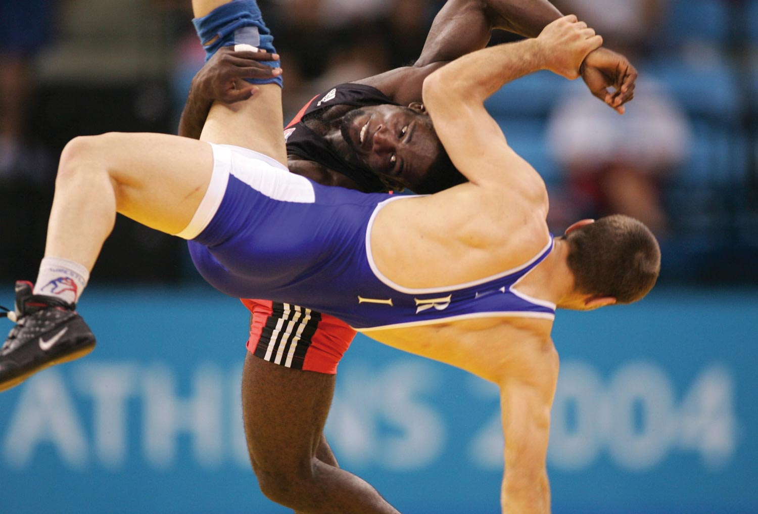 Cuban wrestler Yandro Quintana, red, defeats Masuod Jokar to win gold in the men`s freestyle 60kg at the 2004 Summer Olympics. Photograph courtesy Andreas Rentz/Bongarts/Getty Images