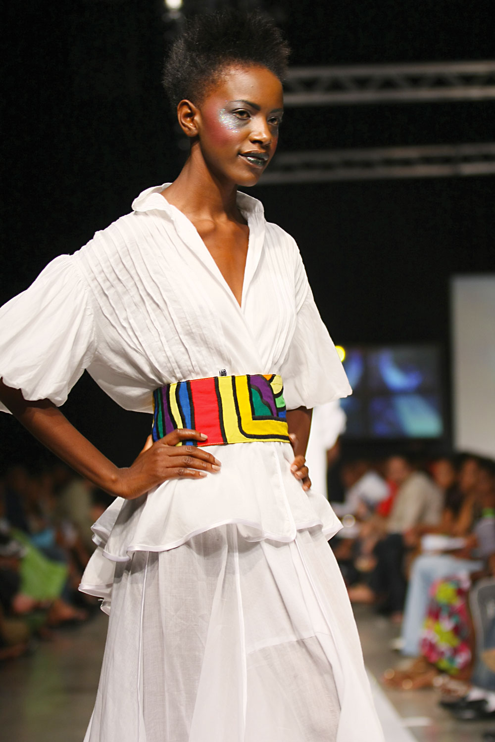 Oreintha Russell in a satin voile tucked blouse with puff sleeves, toucan appliquéd belt and full skirt. Photograph courtesy Caribbean Fashion Week