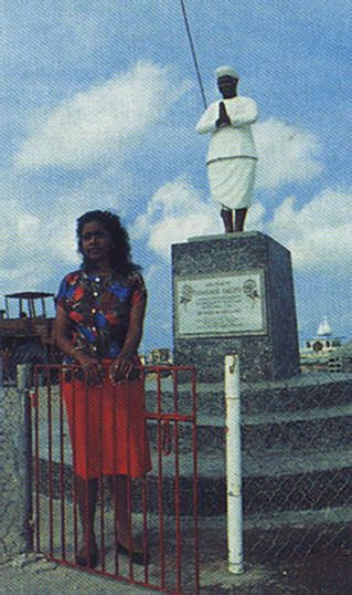 Sadhu's daughter Indrawati stands beside the statue of her father, erected last year as part of the celebrations making the 150th anniversary of the first Indian arrivals in Trinidad. Photograph by Sean Drakes